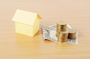 bostadslån koncept med dollar pengar och mynt stack på trä skrivbord bakgrund foto