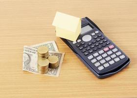 miniräknare och hempapper med dollarpengar och myntbunt på träskrivbord för lånebegrepp foto