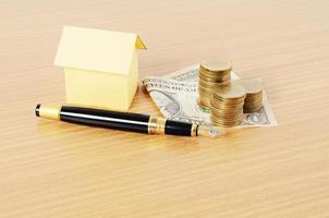 affärsreservoarpenna med huspapper och pengarmyntbunt på träskrivbord för lånekoncept foto