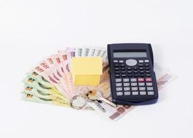 miniräknare och hempapper med nycklar och thailändsk pengarsedel för lånekoncept foto