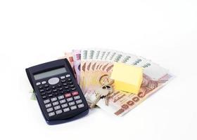 miniräknare och hempapper med nycklar på thailändsk pengarsedel för lånekoncept foto