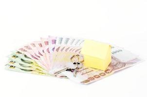 hempapper och nycklar på thailändska sedlar för begrepp för bostadslån foto