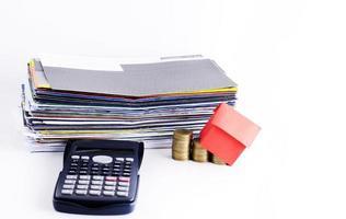 lånekoncept med räkningsbetalning och kalkylator med huspapper och mynt foto