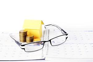 lån koncept med glasögon och pengar mynt stack och papper hus på kalendern boksidor foto