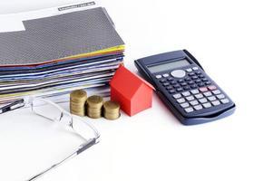 lån koncept med närbild av hus papper och mynt stack med miniräknare och glasögon för bill betalning koncept foto
