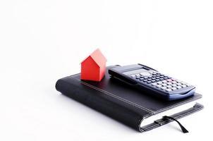 rött huspapper och miniräknare på affärsbok på vit bakgrund foto