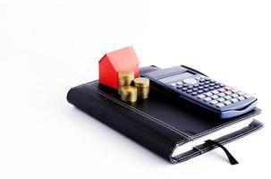 miniräknare och affärsbok med myntbunt och rött huspapper för lånekoncept foto