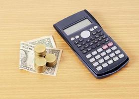 miniräknare och dollarmyntmynt staplar på träskrivbordet foto