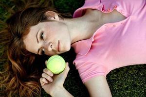 flickasammanträde på gräsmattan på ett tennisfält med en tennisracket foto