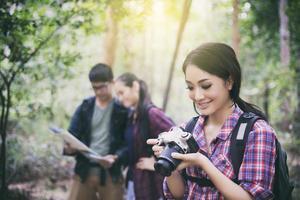 grupp unga vänner som vandrar i skogen foto