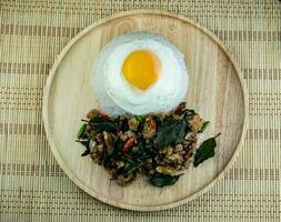 ris toppad kryddstekt fläsk med basilikablad toppad, stekta ägg på en träfat, pad krapow moo är traditionell thailändsk mat foto
