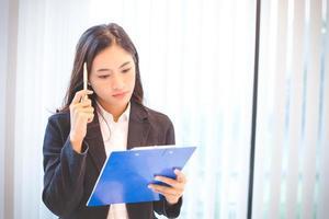 asiatisk kvinna som tittar på klippbrädan för arbete foto