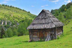ensamt gammalt trähus på en bergskulle med grönt gräs mot blå himmel foto