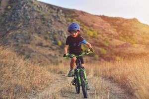 glad unge pojke på 7 år att ha kul i höst park med en cykel på vackra höst dag aktivt barn bär cykel hjälm foto