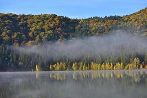 höstlandskap i bergen med träd som reflekterar i vattnet vid st ana lake romania foto