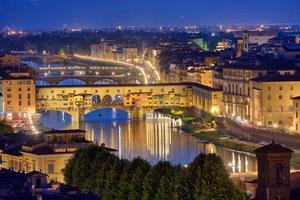 nattvy av floden arno och berömda bron ponte vecchio foto