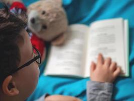 litet barn som läser en bok hemma med sin leksaknallebjörn foto