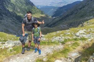 far och son på toppen av berget vandra med ryggsäckar på solig dag foto