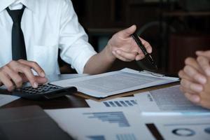 ekonomiska forskningsdiskussioner, affärsteam analyserar inkomstdiagram och diagram för att planera marknadsföringskoncept med hjälp av miniräknare för analys. foto