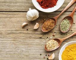 ett urval av olika färgglada kryddor på ett träbord i skålar och skedar foto
