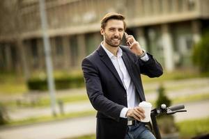 avslappnad affärsman som håller en kaffe och pratar i telefon på en skoter foto