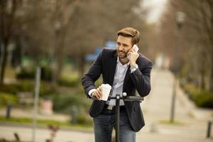 avslappnad affärsman som rider på en skoter medan du håller en kaffe och pratar i telefon foto