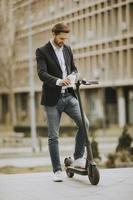 avslappnad affärsman som håller en kaffe och smsar på en skoter foto