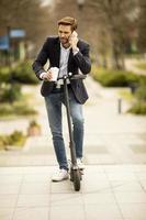 avslappnad affärsman som håller en kaffe och pratar i telefon medan han står på en skoter foto