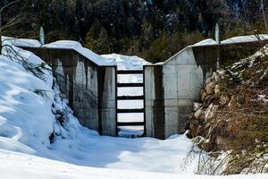 dammen öppen på en bäck och täckt av snö foto