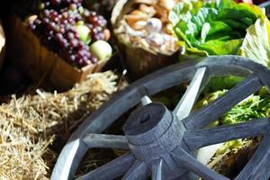sortiment av färska grönsaker på hö med gammalt trähjul foto