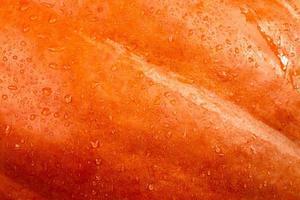 närbild abstrakt texturerad bakgrund av en orange pumpa foto
