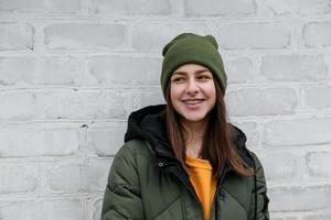 porträtt av en vacker leende flicka med hängslen i en gul tröja och khakihatt foto