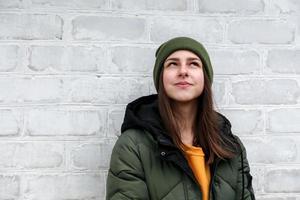 porträtt av en vacker eftertänksam flicka i en gul tröja och khakihatt foto