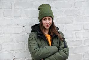 porträtt av en vacker blyg flicka i en gul tröja och khakihatt foto