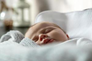 ett närbild porträtt av en flicka som sover i en vagga eller spjälsäng foto