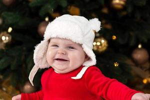 en söt liten flicka i en röd klänning och vit hatt uttrycker känslor foto