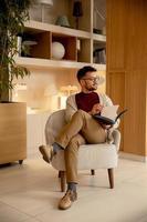 stilig ung man i avslappnade kläder och med glasögon som läser en bok foto
