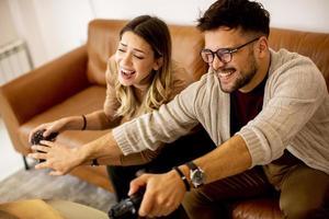 ungt par som spelar videospel hemma sitter på soffan och trivs foto