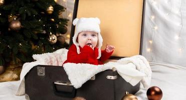 barnet sitter i en gammal resväska foto