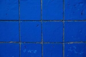liten blå vittrad och skadad kakel vägg bakgrundsstruktur foto