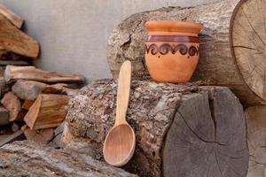 traditionella keramiska kannor och träsked på dekorativ handduk mot trä foto