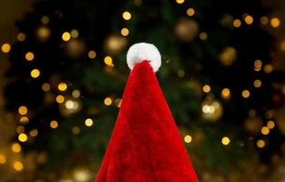 santa hatt på bakgrunden av ett julgran och kransar foto
