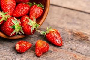 träskål full av färska jordgubbar på det bruna bordet foto