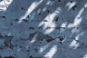 konsistens från gammal grov grungevittrad vägg med sprickor och ljus skugga foto