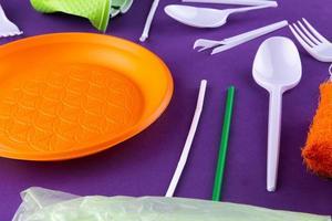 orange, vita och gröna förpackningar av plastprodukter på lila bakgrund foto