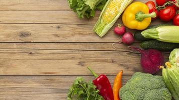 platt låg grönsaker på träbord foto
