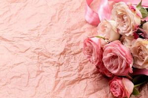 en bukett med vackra rosor på en rosa hantverksbakgrund med plats för text foto