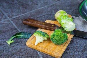 rå broccoli skuren i en träskärbräda foto