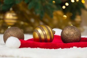 gyllene struntsaker på jultomtenhatt och julgran foto