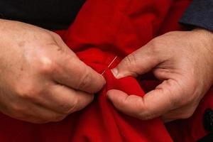 sy med nål och tråd hemma foto
